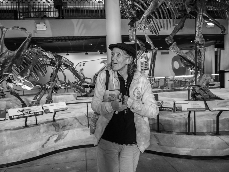 A smiling woman stands in front of dinosaur bones at a museum